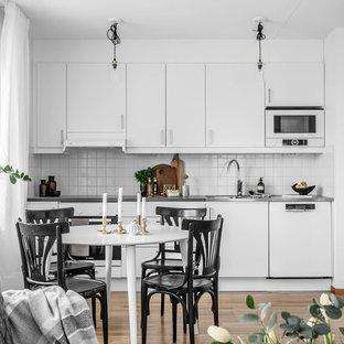Exempel på ett skandinaviskt grå linjärt grått kök med öppen planlösning, med släta luckor, vita skåp, bänkskiva i rostfritt stål, vitt stänkskydd, beiget golv, vita vitvaror och ljust trägolv