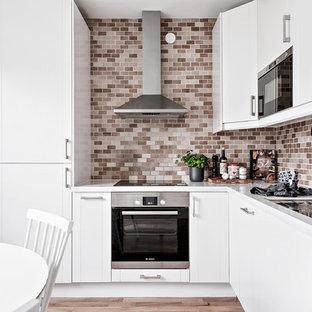 Exempel på ett nordiskt kök, med en dubbel diskho, släta luckor, vita skåp, brunt stänkskydd, stänkskydd i tunnelbanekakel, svarta vitvaror, ljust trägolv och brunt golv