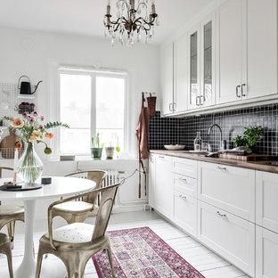 Idéer för nordiska kök och matrum, med skåp i shakerstil, vita skåp, träbänkskiva, svart stänkskydd, målat trägolv och vitt golv