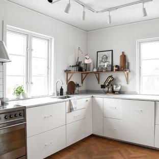 Inspiration för avskilda skandinaviska grått l-kök, med släta luckor, vita skåp, mellanmörkt trägolv, brunt golv, en undermonterad diskho, vitt stänkskydd och rostfria vitvaror