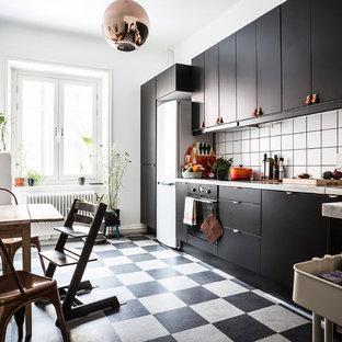 Inspiration för mellanstora nordiska linjära kök, med släta luckor, svarta skåp, vitt stänkskydd, en enkel diskho och klinkergolv i keramik