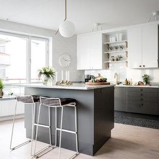 Idéer för ett mellanstort nordiskt parallellkök, med släta luckor, marmorbänkskiva, ljust trägolv, en köksö, svarta skåp och vitt stänkskydd