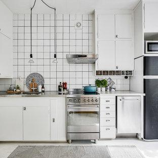 Exempel på ett skandinaviskt grå grått l-kök, med en integrerad diskho, släta luckor, vita skåp, bänkskiva i rostfritt stål, vitt stänkskydd, rostfria vitvaror, målat trägolv och vitt golv
