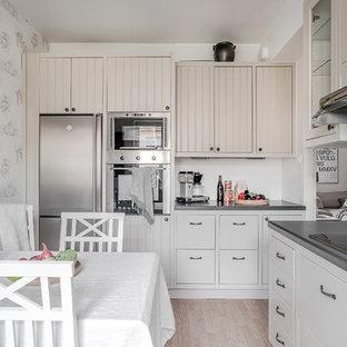 Skandinavisk inredning av ett grå grått kök, med luckor med profilerade fronter, beige skåp, vitt stänkskydd, rostfria vitvaror, ljust trägolv och beiget golv