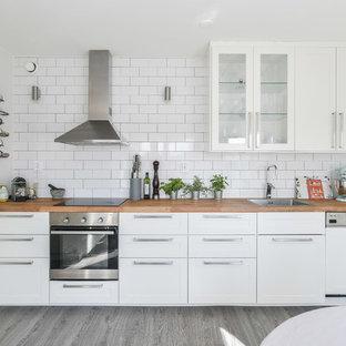 Minimalistisk inredning av ett linjärt kök och matrum, med en enkel diskho, skåp i shakerstil, vita skåp, träbänkskiva, vitt stänkskydd, stänkskydd i tunnelbanekakel och rostfria vitvaror