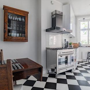 Skandinavisk inredning av ett svart svart kök och matrum, med släta luckor, vita skåp, stänkskydd i glaskakel, rostfria vitvaror och flerfärgat golv