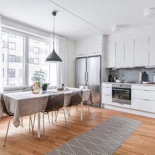 Inspiration för ett funkis beige beige kök, med en undermonterad diskho, släta luckor, vita skåp, grått stänkskydd, rostfria vitvaror, mellanmörkt trägolv och brunt golv