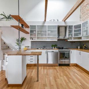 Foto på ett nordiskt brun l-kök, med en nedsänkt diskho, släta luckor, vita skåp, träbänkskiva, grått stänkskydd, rostfria vitvaror, mellanmörkt trägolv, brunt golv och en halv köksö