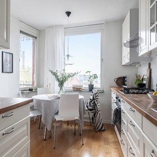 Exempel på ett minimalistiskt kök, med en dubbel diskho, vita skåp, träbänkskiva, vitt stänkskydd, stänkskydd i tunnelbanekakel och ljust trägolv