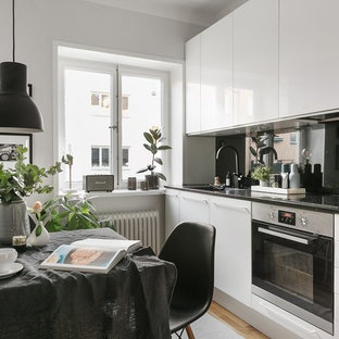 Small modern kitchen designs - Example of a small minimalist single-wall kitchen design in Stockholm with flat-panel cabinets and white cabinets