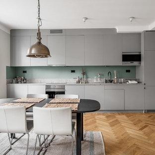 Bild på ett mellanstort skandinaviskt linjärt kök och matrum, med släta luckor, grå skåp, grönt stänkskydd, rostfria vitvaror, mellanmörkt trägolv och marmorbänkskiva