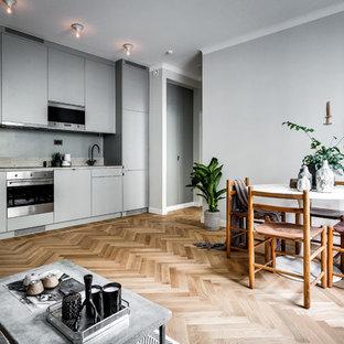 Diseño de cocina lineal, nórdica, grande, abierta, sin isla, con armarios con paneles lisos, puertas de armario grises, suelo de madera clara y salpicadero verde