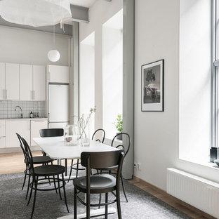 Bild på ett stort minimalistiskt kök, med släta luckor, vita skåp, vita vitvaror, mellanmörkt trägolv och beiget golv