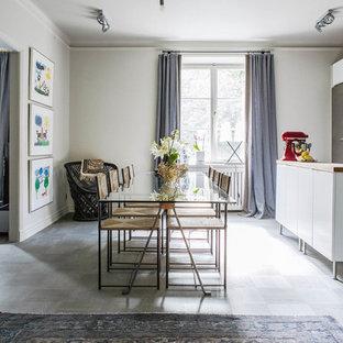 Foto på ett mellanstort skandinaviskt kök, med släta luckor, vita skåp, träbänkskiva, rostfria vitvaror, en köksö och kalkstensgolv