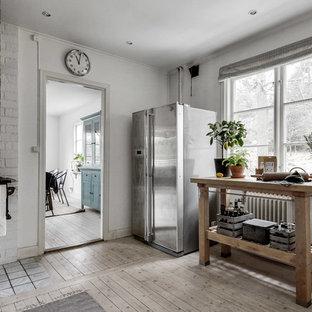 Inspiration för mellanstora rustika linjära kök, med ljust trägolv och en köksö