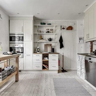 Bild på ett avskilt, mellanstort lantligt l-kök, med skåp i shakerstil, beige skåp, träbänkskiva, vitt stänkskydd, rostfria vitvaror, ljust trägolv och en köksö