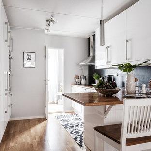 Bild på ett nordiskt brun brunt l-kök, med släta luckor, vita skåp, träbänkskiva, svart stänkskydd, mellanmörkt trägolv, en halv köksö och brunt golv
