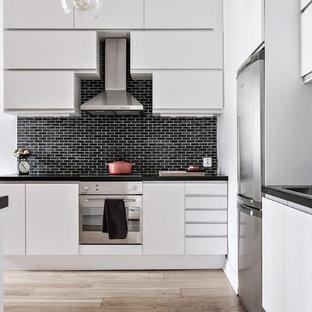 Idéer för att renovera ett funkis linjärt kök, med släta luckor, vita skåp, svart stänkskydd, stänkskydd i tegel och rostfria vitvaror