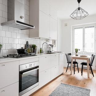 Idéer för mellanstora minimalistiska linjära kök med öppen planlösning, med en nedsänkt diskho, släta luckor, vita skåp, laminatbänkskiva, vitt stänkskydd, stänkskydd i porslinskakel, rostfria vitvaror och mellanmörkt trägolv
