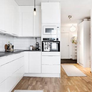 Skandinavisk inredning av ett mellanstort kök, med släta luckor, vita skåp, vitt stänkskydd och ljust trägolv