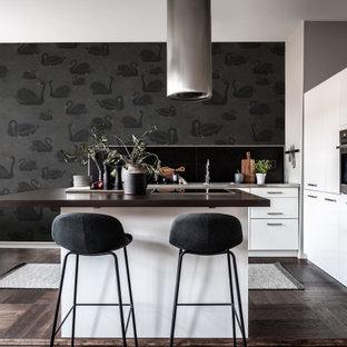 Idéer för mellanstora funkis brunt l-kök, med släta luckor, vita skåp, rostfria vitvaror, en köksö och brunt golv