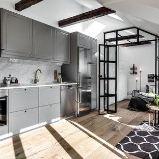 Foto på ett mellanstort industriellt linjärt kök med öppen planlösning, med luckor med upphöjd panel, grå skåp, grått stänkskydd, rostfria vitvaror och ljust trägolv