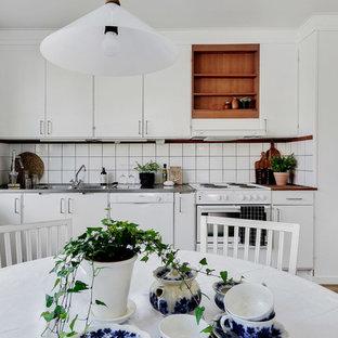 Idéer för att renovera ett nordiskt brun brunt kök, med en integrerad diskho, släta luckor, vita skåp, träbänkskiva, vitt stänkskydd, vita vitvaror, mellanmörkt trägolv och brunt golv