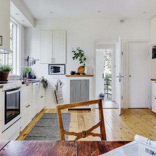Inspiration för skandinaviska brunt kök, med en undermonterad diskho, luckor med upphöjd panel, vita skåp, träbänkskiva, vitt stänkskydd, stänkskydd i tunnelbanekakel, vita vitvaror, ljust trägolv och brunt golv