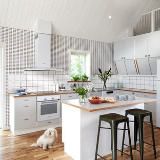 This is an example of a midcentury l-shaped open plan kitchen in Gothenburg with with island.
