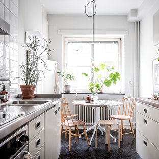 This is an example of a small scandinavian galley kitchen/diner in Gothenburg with flat-panel cabinets, grey cabinets, stainless steel worktops, white splashback, lino flooring, no island and black floors.