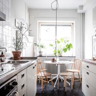 Idéer för ett litet minimalistiskt kök, med släta luckor, grå skåp, bänkskiva i rostfritt stål, vitt stänkskydd, linoleumgolv och svart golv