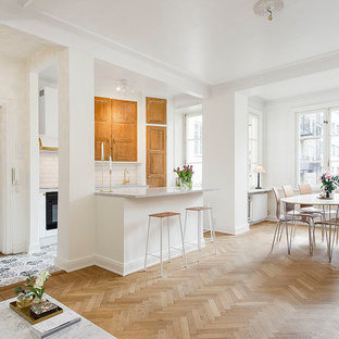 Inspiration for a mid-sized scandinavian single-wall open plan kitchen in Stockholm with raised-panel cabinets, medium wood cabinets, white splashback, subway tile splashback, light hardwood floors, with island, marble benchtops and black appliances.