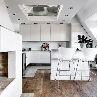 Idéer för att renovera ett litet nordiskt grå grått kök, med släta luckor, vita skåp, rostfria vitvaror, mellanmörkt trägolv, en köksö och brunt golv