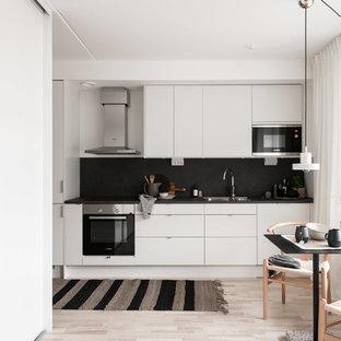 Inredning av ett nordiskt litet svart linjärt svart kök och matrum, med en dubbel diskho, släta luckor, vita skåp, svart stänkskydd, stänkskydd i skiffer, integrerade vitvaror, ljust trägolv och beiget golv