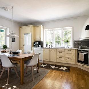 Bild på ett mellanstort skandinaviskt grå grått kök, med luckor med upphöjd panel, beige skåp, grått stänkskydd, mellanmörkt trägolv och brunt golv