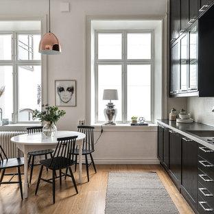 Idéer för skandinaviska linjära grått kök och matrum, med skåp i shakerstil, svarta skåp, vitt stänkskydd, stänkskydd i mosaik, rostfria vitvaror, ljust trägolv och beiget golv