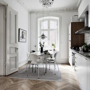 Foto på ett stort nordiskt linjärt kök och matrum, med en enkel diskho, släta luckor, vita skåp, vitt stänkskydd, stänkskydd i tunnelbanekakel, integrerade vitvaror, mellanmörkt trägolv och brunt golv