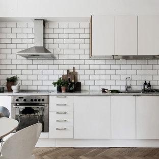 Exempel på ett minimalistiskt linjärt kök och matrum, med släta luckor, vita skåp, vitt stänkskydd, stänkskydd i tunnelbanekakel, integrerade vitvaror, mellanmörkt trägolv och brunt golv