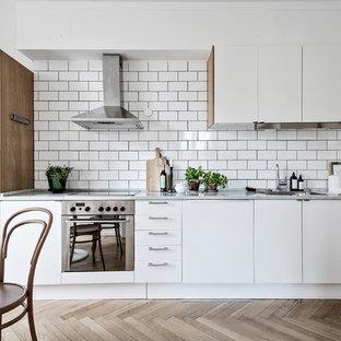 Inredning av ett minimalistiskt linjärt kök och matrum, med släta luckor, vita skåp, mellanmörkt trägolv, beiget golv, en enkel diskho, vitt stänkskydd, stänkskydd i tunnelbanekakel och rostfria vitvaror