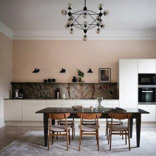 Minimalistisk inredning av ett grå linjärt grått kök och matrum, med släta luckor, vita skåp, grått stänkskydd, stänkskydd i sten, svarta vitvaror, mörkt trägolv och brunt golv