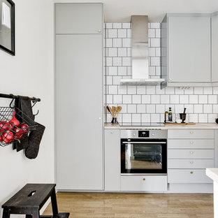Idéer för att renovera ett skandinaviskt u-kök, med släta luckor, grå skåp, vitt stänkskydd, rostfria vitvaror, ljust trägolv och beiget golv