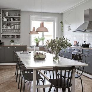 Skandinavisk inredning av ett linjärt kök och matrum, med släta luckor, grå skåp, träbänkskiva, vitt stänkskydd, stänkskydd i tunnelbanekakel, rostfria vitvaror, mellanmörkt trägolv och brunt golv