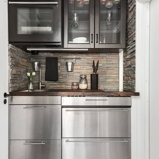 Small contemporary enclosed kitchen pictures - Small trendy single-wall medium tone wood floor enclosed kitchen photo in Stockholm with a single-bowl sink, glass-front cabinets, stainless steel cabinets, wood countertops, stainless steel appliances and no island
