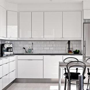 Minimalistisk inredning av ett mellanstort l-kök, med vita skåp och vita vitvaror