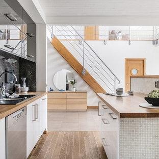Idéer för att renovera ett funkis brun brunt kök, med en nedsänkt diskho, släta luckor, vita skåp, träbänkskiva, svart stänkskydd, stänkskydd i mosaik, svarta vitvaror, mellanmörkt trägolv, en köksö och brunt golv