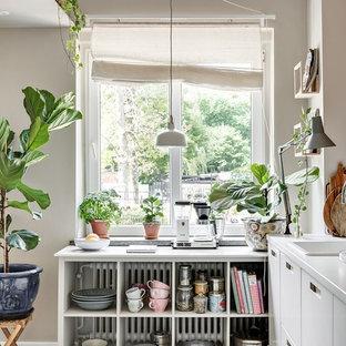 Skandinavisk inredning av ett litet vit vitt l-kök, med släta luckor, en nedsänkt diskho, vita skåp, integrerade vitvaror, betonggolv och grått golv