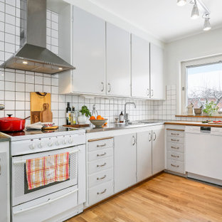 Inspiration för ett avskilt, mellanstort 50 tals grå grått u-kök, med en dubbel diskho, släta luckor, grå skåp, bänkskiva i rostfritt stål, vitt stänkskydd, rostfria vitvaror, mellanmörkt trägolv och brunt golv