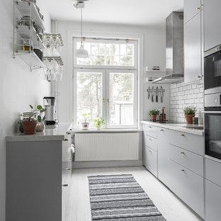 Foto på ett nordiskt vit linjärt kök, med en undermonterad diskho, släta luckor, grå skåp, vitt stänkskydd, stänkskydd i tunnelbanekakel och vitt golv