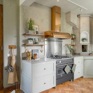 Bild på ett lantligt kök, med luckor med infälld panel, gröna skåp, granitbänkskiva, stänkskydd med metallisk yta och mellanmörkt trägolv
