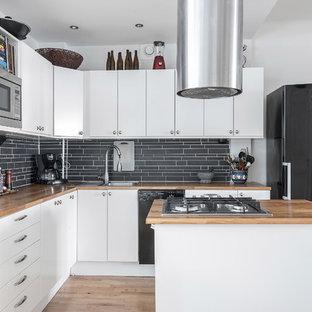 Idéer för att renovera ett mellanstort minimalistiskt brun brunt l-kök, med släta luckor, vita skåp, träbänkskiva, svart stänkskydd, stänkskydd i stickkakel, ljust trägolv, beiget golv, en nedsänkt diskho, svarta vitvaror och en köksö